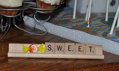 """Sweet"" spelled out on a Scrabble letter holder and the Candy Land styrofoam cheesecake pop holder"