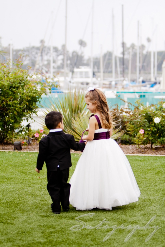 Flower girl and ring bearer walking together up the aisle, photo by Sutography